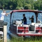 Boys fishing from pontoon boat.